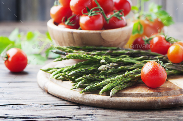 Uncooked asparagus with tomato on the wooden table - Stock Photo - Images
