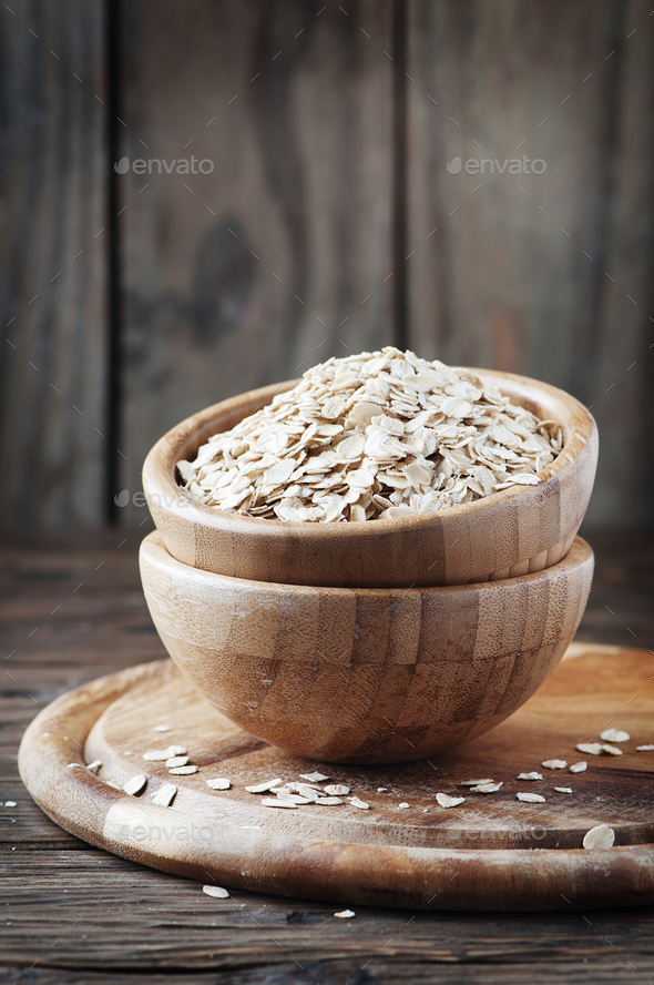Uncooked oatmeal on the wooden table - Stock Photo - Images