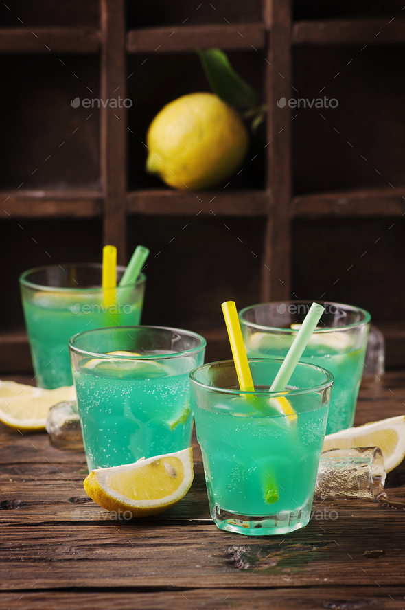Green cocktail with lemon and ice on the wooden table - Stock Photo - Images