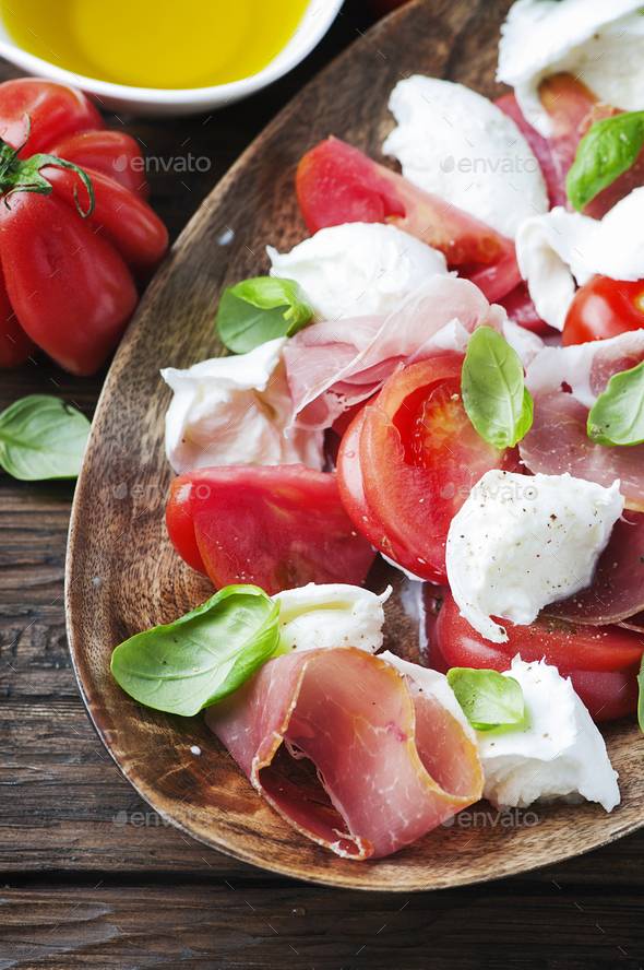 Italian salad caprese with ham, basil and mozzarella - Stock Photo - Images