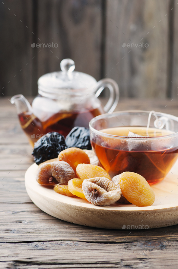 Mix of dried fruits with cup of black tea - Stock Photo - Images