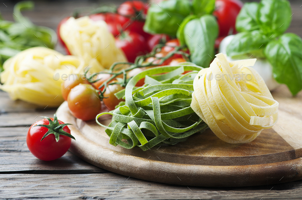 Raw pasta, tomato and basil on the wooden table - Stock Photo - Images