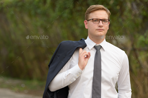Businessman with blond hair in the streets outdoors - Stock Photo - Images