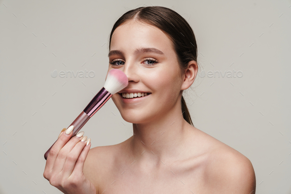 Image of pleased cute shirtless woman using makeup brush and smiling - Stock Photo - Images