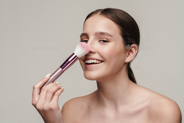 Image of pleased cute shirtless woman using makeup brush and laughing - Stock Photo - Images