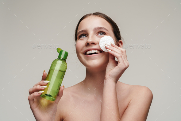 Image of pleased young shirtless woman using face lotion and smiling - Stock Photo - Images