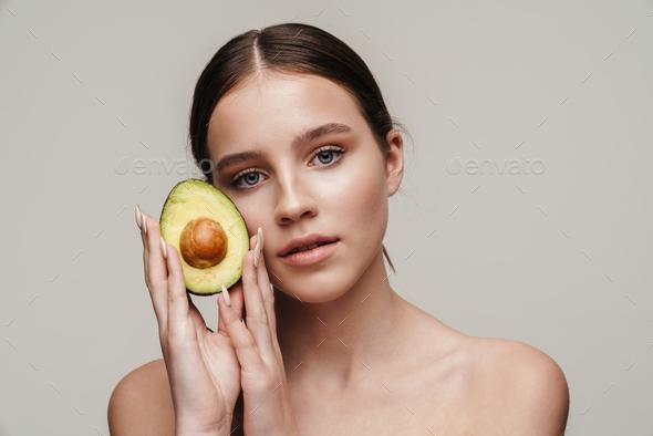 Image of beautiful shirtless woman posing with avocado at camera - Stock Photo - Images