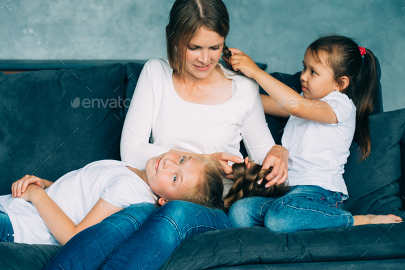 Family together happy. Mother with two daughters home relaxing playing. Family portrait. - Stock Photo - Images