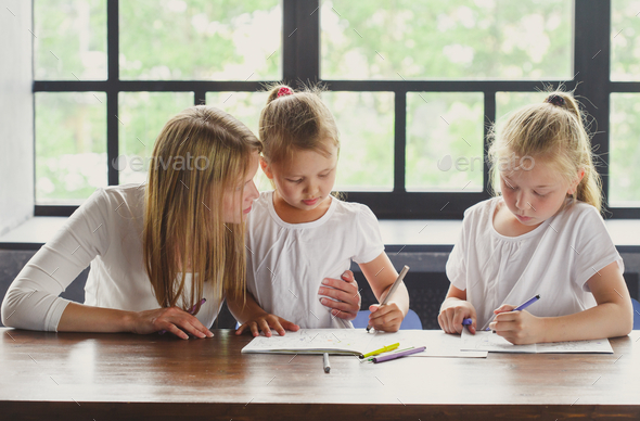 Mother with daughters help lessons learned. Family portrait - Stock Photo - Images