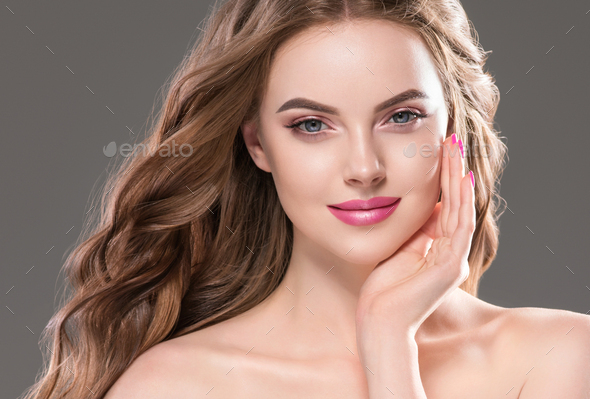 Beautiful woman with long curly brunette hair over gray background. Studio shot. - Stock Photo - Images