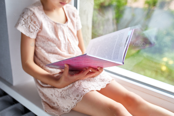 Cute little girl reading book at home, at windowsill - Stock Photo - Images