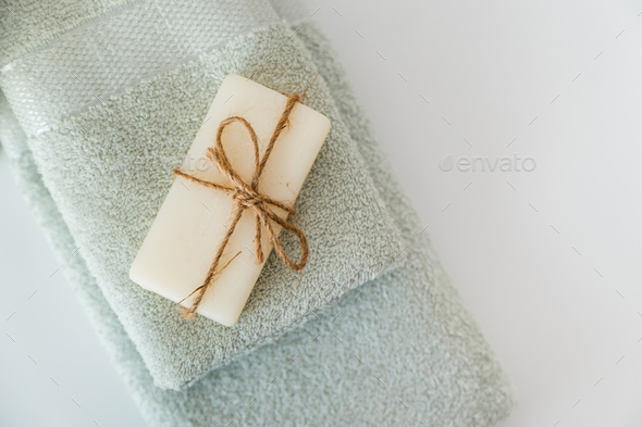 Solid soap corded on bath towels on white background with copy space. Top view with copy space - Stock Photo - Images