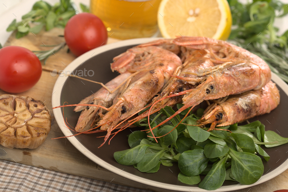 Boiled shrimp with fresh tomatoes and leaves of salad on ceramic plate. Top view. - Stock Photo - Images