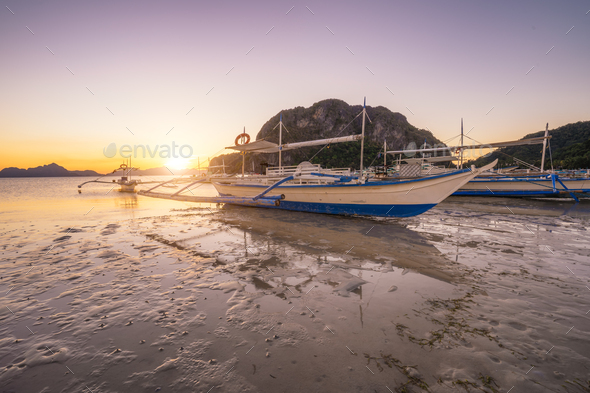 Trip long banca boat on Corong corong beach, sunset flare shine. El Nido, Philippines - Stock Photo - Images