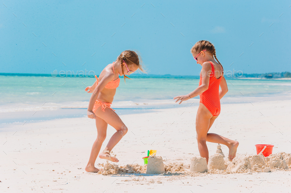 Little happy funny girls have a lot of fun at tropical beach playing together - Stock Photo - Images