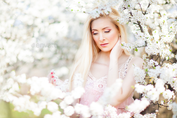 Young beautiful blonde smiling woman in white mini dress standing with blooming trees at background - Stock Photo - Images