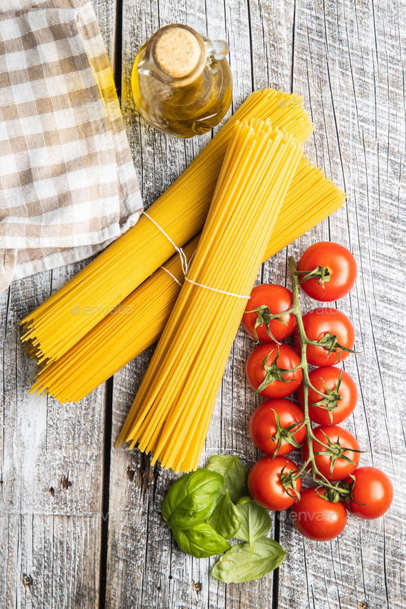 Raw spaghetti pasta, cherry tomatoes, basil leaves and olive oil. - Stock Photo - Images
