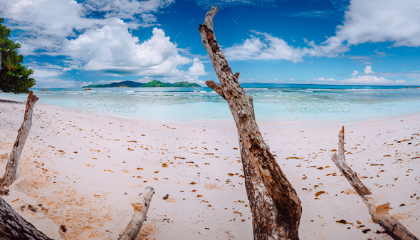 Impressive cloudscape above tropical island Praslin. Panorama of white sand paradise beach of anse - Stock Photo - Images