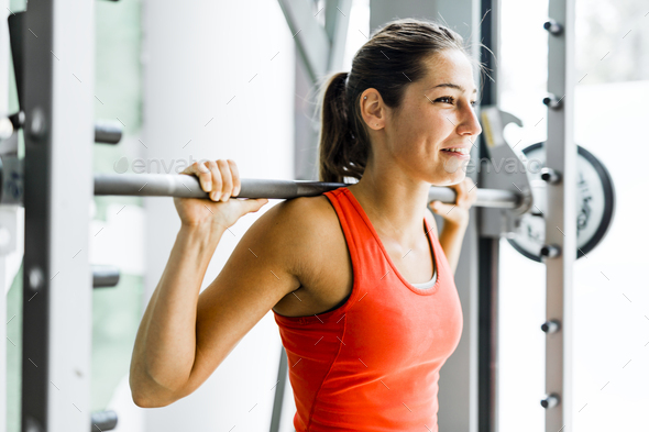 Young beautiful woman lifting weights in a gym - Stock Photo - Images
