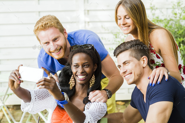 A group of friends sitting a table and talking smiling while ta - Stock Photo - Images