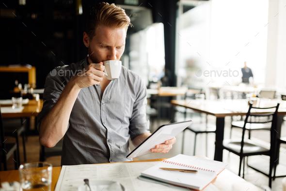 Businessman reading on break - Stock Photo - Images