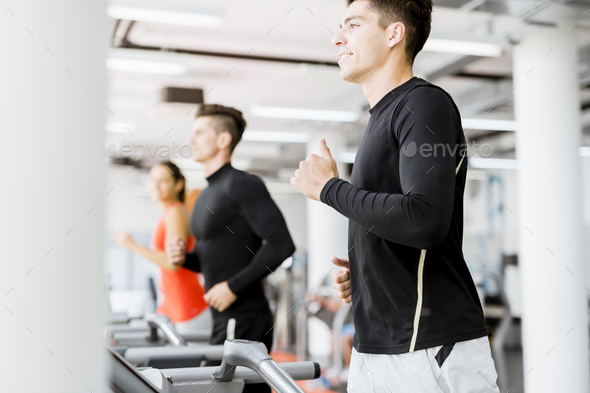 Group of young people using treadmills in a gym - Stock Photo - Images