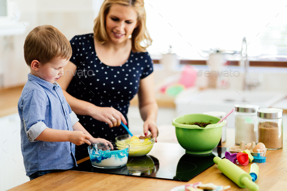 Mother and child preparing cookies in kitchen - Stock Photo - Images