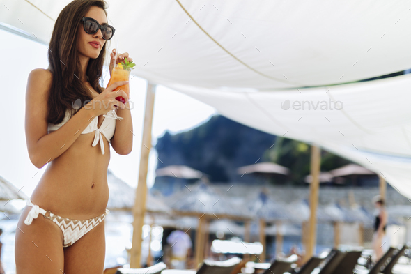 Stunning woman drinking cocktail on beach - Stock Photo - Images