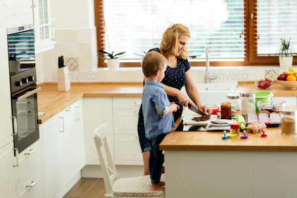 Child helping mother make cookies - Stock Photo - Images