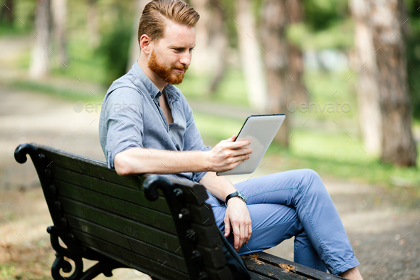Businessman using tablet pc in nature - Stock Photo - Images