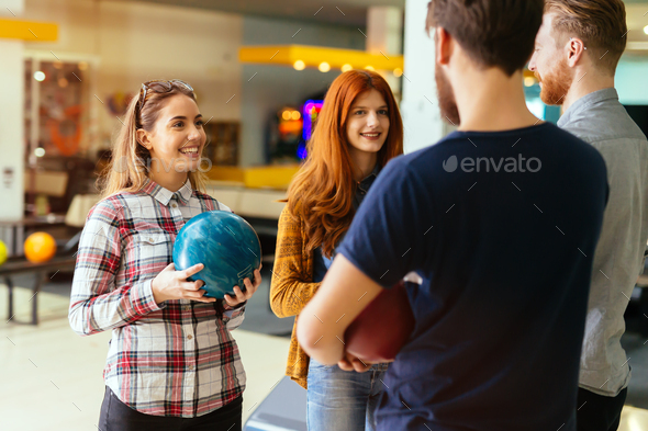 Cheerful friends bowling together - Stock Photo - Images