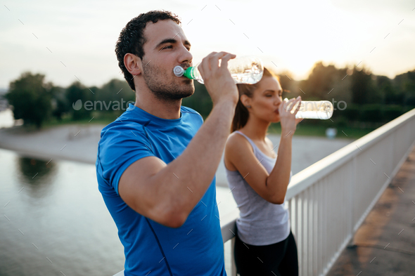 Athletic couple drinking water - Stock Photo - Images