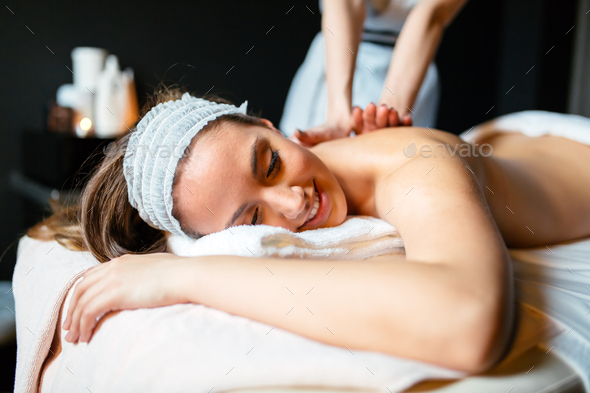 Beautiful young and cute woman enjoying massage treatment - Stock Photo - Images