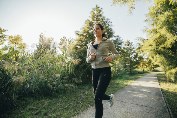 Fit beautiful woman jogging in park - Stock Photo - Images