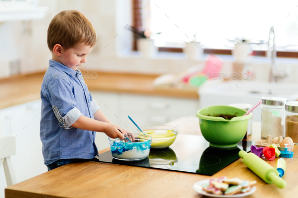 Cute child learning to become a chef since the age of 2 - Stock Photo - Images