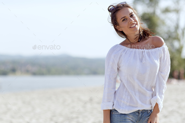 Beautiful young woman posing on a windy summer day - Stock Photo - Images