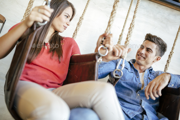 Young couple relaxing in swing - Stock Photo - Images