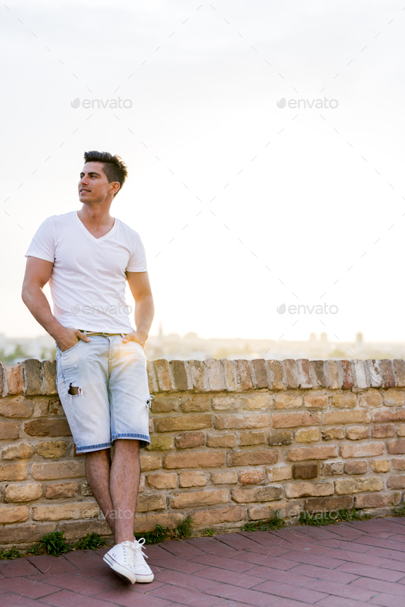 Handsome young man leaning against a brick wall - Stock Photo - Images