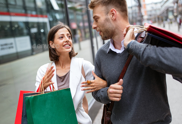 Beautiful young loving couple walking by the street with shopping bags - Stock Photo - Images