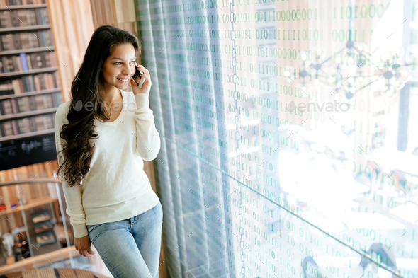 Beautiful businesswoman using phone indoors and smiling - Stock Photo - Images