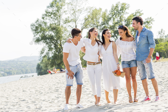 Group of young people holding hands on beach - Stock Photo - Images