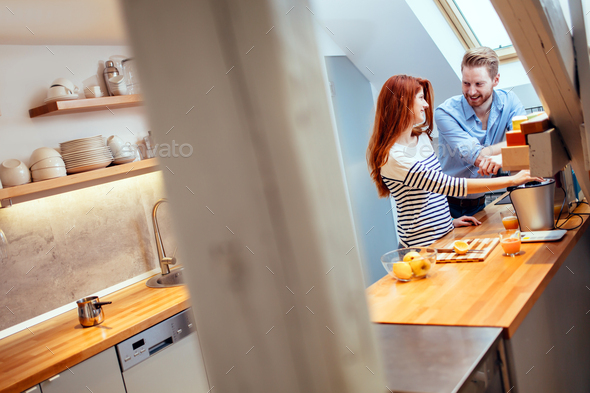 Attractive couple in kitchen - Stock Photo - Images