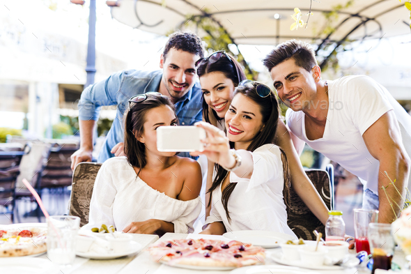 Group of young beautiful people sitting in a restaurant and taki - Stock Photo - Images