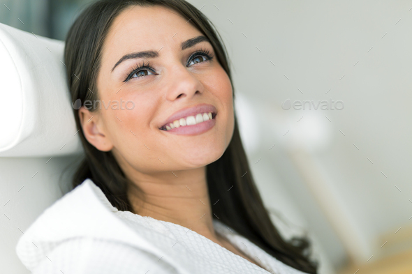 Portrait of a beautiful young woman relaxing in a robe - Stock Photo - Images