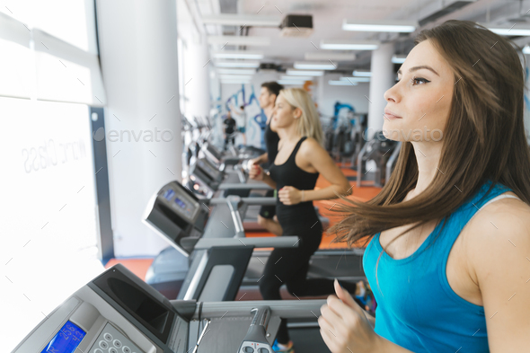 People running on treadmills in gym - Stock Photo - Images
