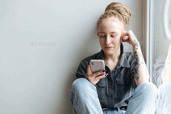 Girl with dreadlocks and piercing using mobile phone - Stock Photo - Images
