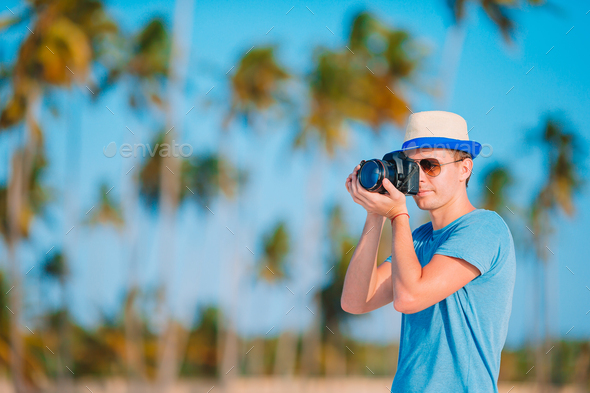 Young man photographed at camera on tropical beach - Stock Photo - Images