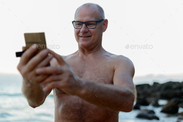 Mature handsome tourist man shirtless at the beach - Stock Photo - Images