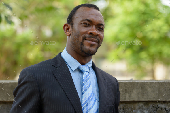 Portrait of handsome African bearded businessman outdoors - Stock Photo - Images
