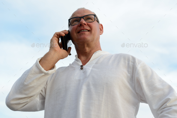 Mature handsome tourist man against view of the beach outdoors - Stock Photo - Images